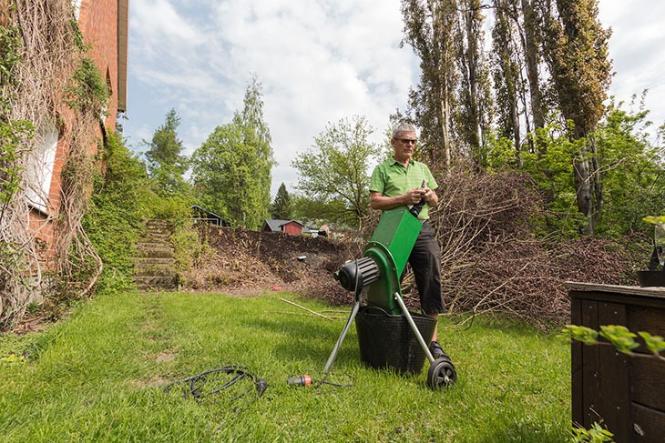 A man in a garden with a wood chipper