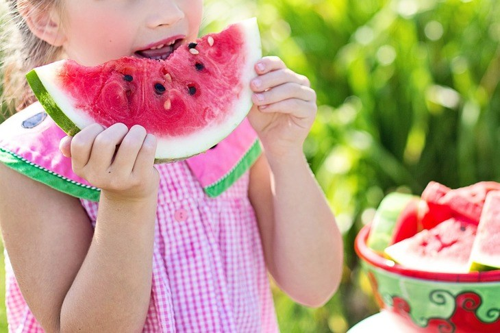 A little girl eating a watermelon with some seeds