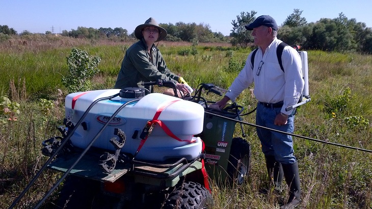 A man and woman calibrating their ATV sprayer before using it in their field