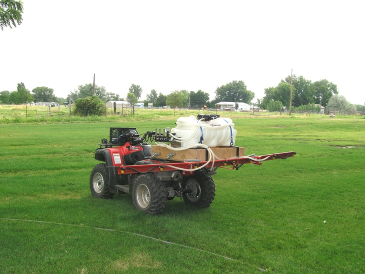 The sprayer is mounted on a wooden platform that is bolted on the ATV's metal racks