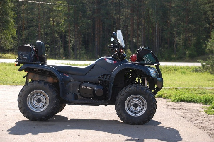 This is an image of an ATV with a metal rear rack. This type of ATV can secure at least an 8 Gallon sprayer