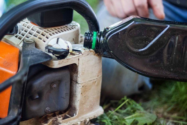 A lumberjack fills his gas-powered chainsaw with gasoline to continue working