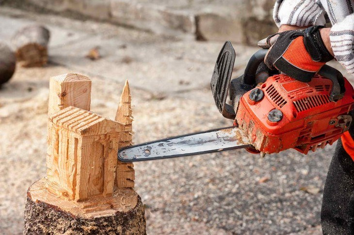 A wood sculptor uses a chainsaw as his tool for his project