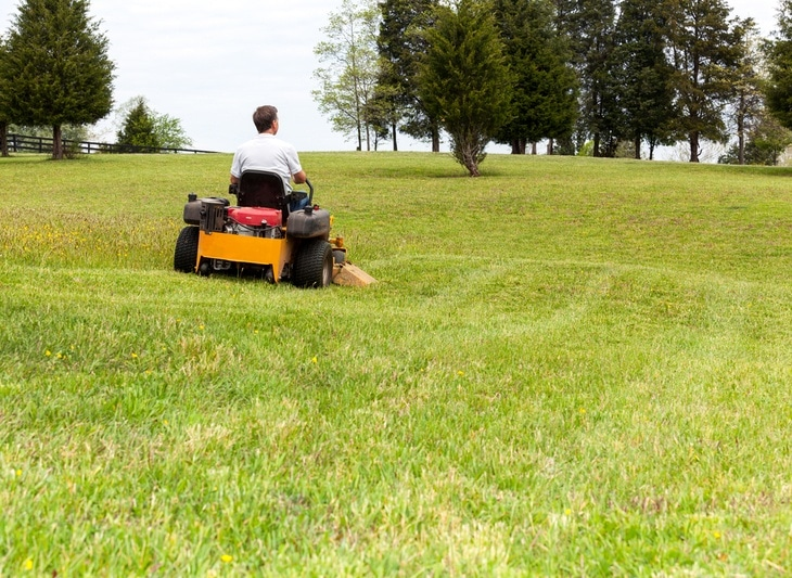A zero turn mower is used to mow a hilly lawn