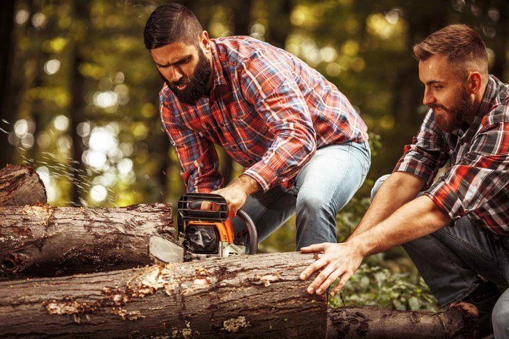 Two lumberjacks are cutting off a log for their cabin