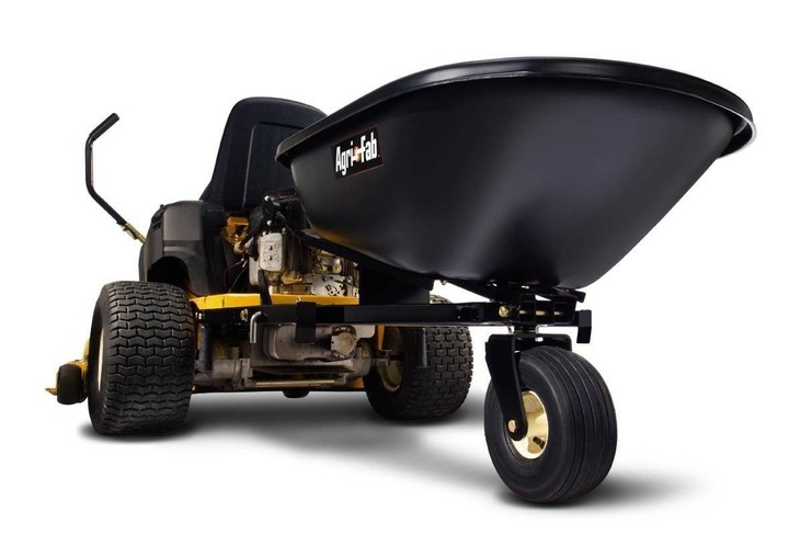 A sample dump cart, one of the attachments, is connected to the rear part of a zero turn mower