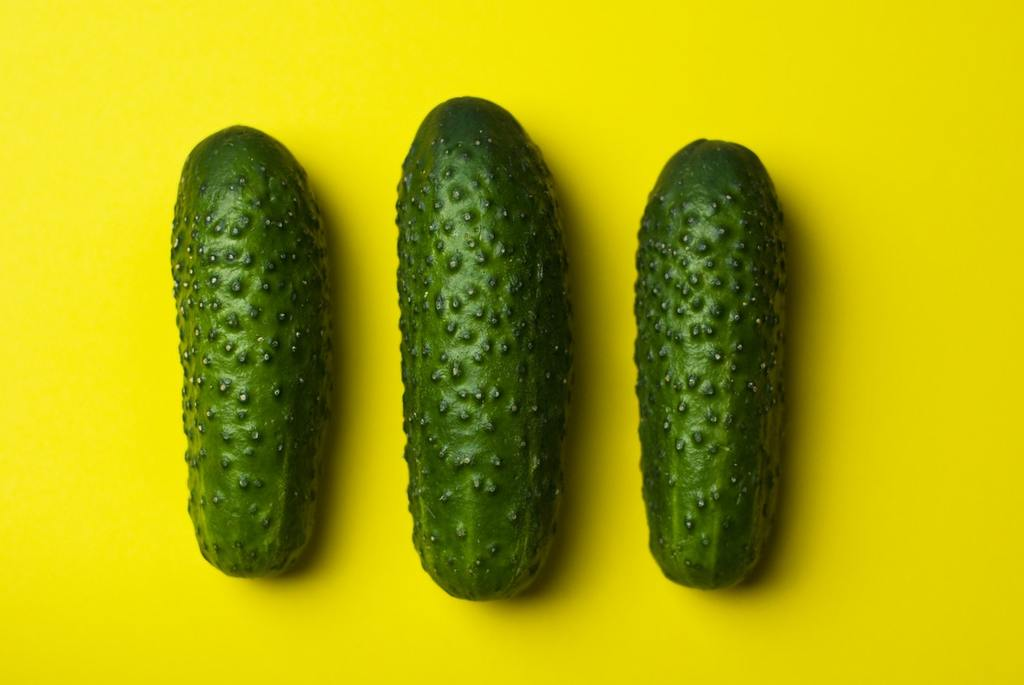 Three cucumbers on top of yellow table
