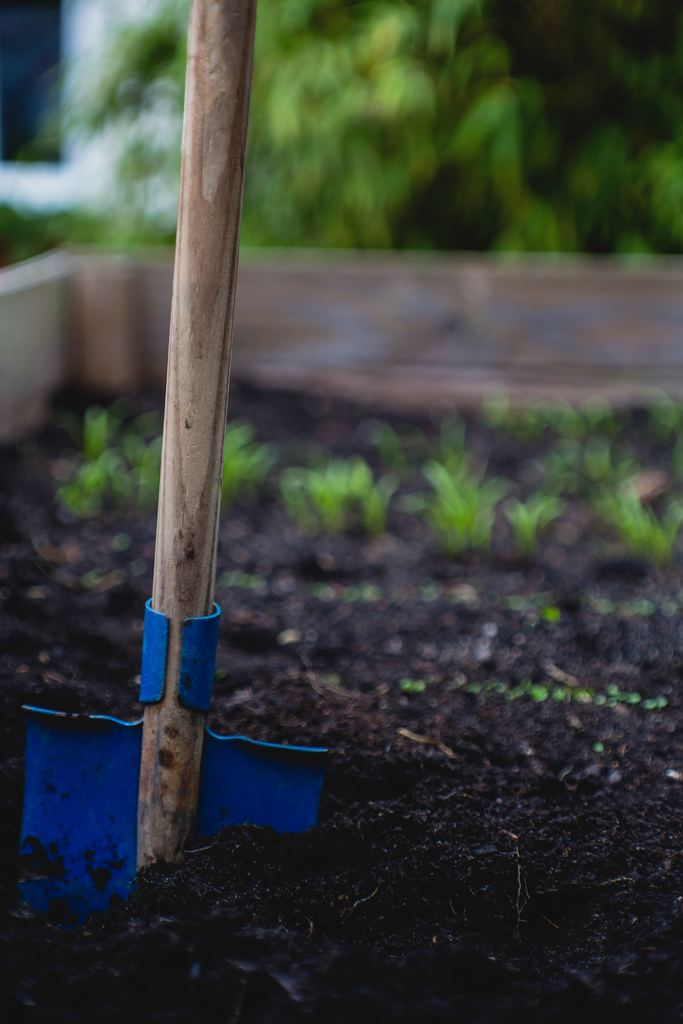a shovel on a plant box used for square foot garden spacing