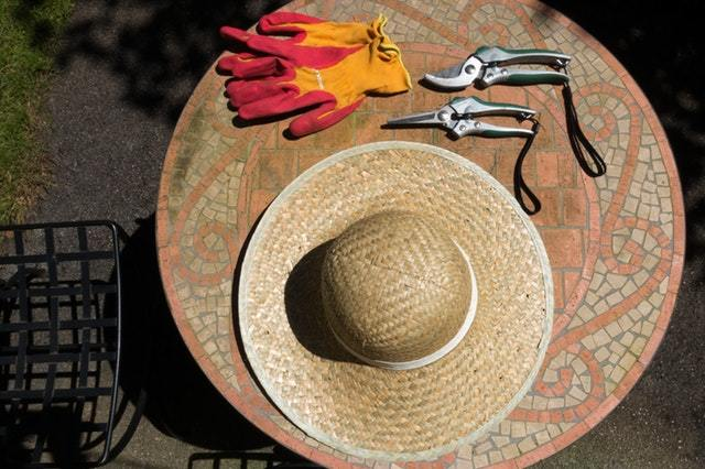 gardening gloves, pruning shears, and a hat on top of a table