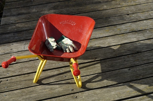 a pair of gardening gloves on wheelbarrow